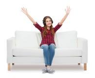 Adolescente que se sienta en el sofá con los auriculares Fotos de archivo libres de regalías