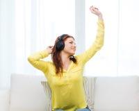 Adolescente que se sienta en el sofá con los auriculares Fotografía de archivo libre de regalías