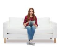 Adolescente que se sienta en el sofá con PC de la tableta Foto de archivo