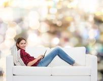 Adolescente que se sienta en el sofá con PC de la tableta Imágenes de archivo libres de regalías