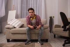 Adolescente que se sienta en el sofá que juega a los juegos de ordenador Fotos de archivo