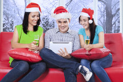 Adolescente que se sienta en el sofá usando la tableta Fotos de archivo libres de regalías