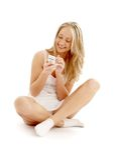 Adolescente que se sienta en el suelo con un teléfono blanco Fotografía de archivo