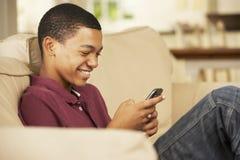 Adolescente que se sienta en el teléfono móvil de Sofa At Home Texting On Foto de archivo libre de regalías