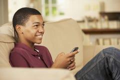 Adolescente que se sienta en el teléfono móvil de Sofa At Home Texting On Fotografía de archivo libre de regalías