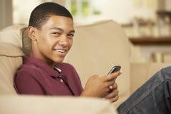 Adolescente que se sienta en el teléfono móvil de Sofa At Home Texting On Foto de archivo