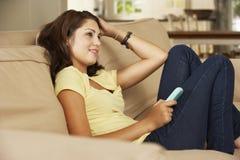 Adolescente que se sienta en el teléfono móvil de Sofa At Home Texting On Fotos de archivo libres de regalías