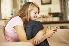 Adolescente que se sienta en el teléfono móvil de Sofa At Home Texting On Imágenes de archivo libres de regalías