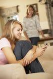 Adolescente que se sienta en el teléfono móvil de Sofa At Home Texting On con la madre en fondo Imagen de archivo libre de regalías