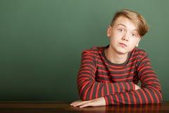Adolescente que se sienta en fondo verde Imagen de archivo