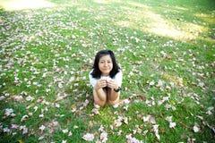 Adolescente que se sienta en hierba Imagen de archivo libre de regalías