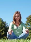 Adolescente que se sienta en hierba Foto de archivo libre de regalías