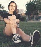 Adolescente que se sienta en hierba Imagenes de archivo