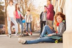 Adolescente que se sienta en la acera con el monopatín Fotografía de archivo
