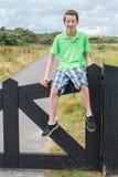 Adolescente que se sienta en la cerca de madera negra en naturaleza Imágenes de archivo libres de regalías