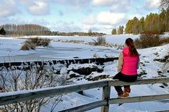 Adolescente que se sienta en la cerca Paisaje hermoso del invierno en fondo Foto de archivo libre de regalías