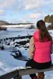 Adolescente que se sienta en la cerca Paisaje hermoso del invierno en fondo Imagen de archivo