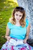 Adolescente que se sienta en la hierba y el libro de lectura Fotografía de archivo