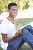 Adolescente que se sienta en la lectura del parque Fotos de archivo libres de regalías