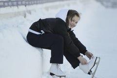 Adolescente que se sienta en la nieve que aprieta los cordones en los patines Imagenes de archivo
