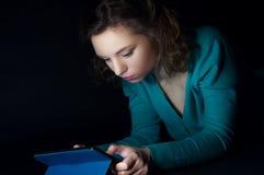Adolescente que se sienta en la noche en Internet Foto de archivo