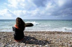 Adolescente que se sienta en la playa Imagen de archivo
