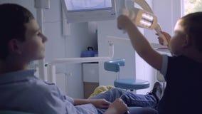 Adolescente que se sienta en la silla en oficina del dentista mientras que su pequeño hermano que juega la lámpara que imita a un metrajes
