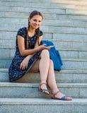Adolescente que se sienta en las escaleras y los controles un smartphone Imágenes de archivo libres de regalías
