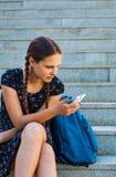 Adolescente que se sienta en las escaleras y los controles un smartphone Foto de archivo libre de regalías
