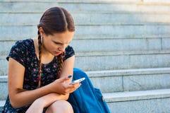 Adolescente que se sienta en las escaleras y los controles un smartphone Fotos de archivo libres de regalías