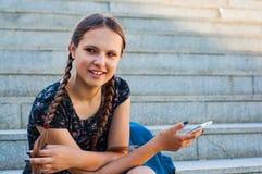 Adolescente que se sienta en las escaleras y los controles un smartphone Foto de archivo