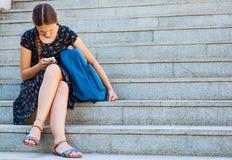 Adolescente que se sienta en las escaleras y que mira en teléfono Fotografía de archivo libre de regalías