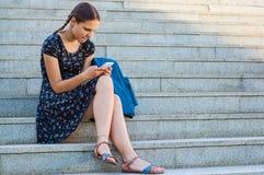 Adolescente que se sienta en las escaleras y que mira en teléfono Fotos de archivo libres de regalías