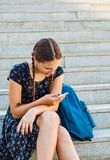 Adolescente que se sienta en las escaleras y que mira en teléfono Imagen de archivo