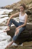 Adolescente que se sienta en las rocas Foto de archivo libre de regalías