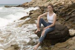 Adolescente que se sienta en las rocas Imagenes de archivo