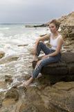 Adolescente que se sienta en las rocas Fotografía de archivo libre de regalías