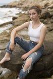 Adolescente que se sienta en las rocas Fotografía de archivo