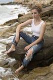 Adolescente que se sienta en las rocas Fotos de archivo libres de regalías