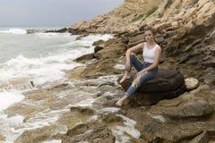 Adolescente que se sienta en las rocas Foto de archivo