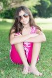 Adolescente que se sienta en los sunglassses que llevan de la hierba Foto de archivo libre de regalías