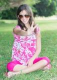Adolescente que se sienta en los sunglassses que llevan de la hierba Fotos de archivo libres de regalías