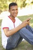 Adolescente que se sienta en mensaje de texto de la lectura del parque en el teléfono móvil Fotos de archivo libres de regalías
