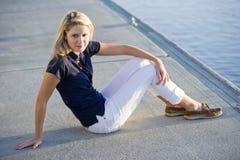 Adolescente que se sienta en muelle por el agua Imagenes de archivo