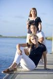 Adolescente que se sienta en muelle por el agua con los padres Foto de archivo