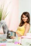 Adolescente que se sienta en ordenador de la tablilla de la cama Fotografía de archivo libre de regalías