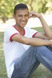 Adolescente que se sienta en parque Imagen de archivo