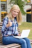 Adolescente que se sienta en parque con el ordenador portátil y los pulgares para arriba Fotografía de archivo libre de regalías