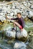 Adolescente que se sienta en piedra Foto de archivo libre de regalías