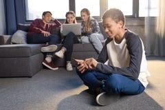Adolescente que se sienta en piso y que usa smartphone con los amigos que usan el ordenador portátil detrás Foto de archivo libre de regalías